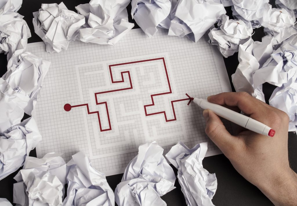 Hand working through a paper maze